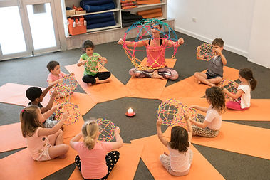 Kids using breathing ball to learn ow to breathe in yoga