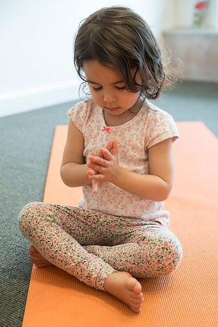 child in yoga pose meditating