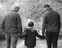 Father and grandfather walks with grandson