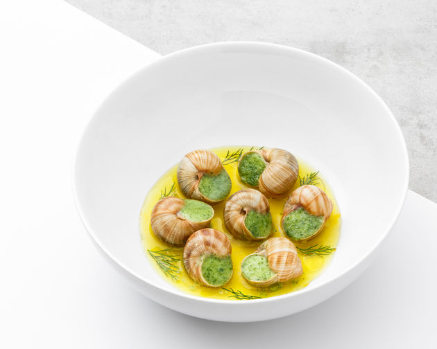 French snail in butter sauce served in a white bowl photographed on white and gray background