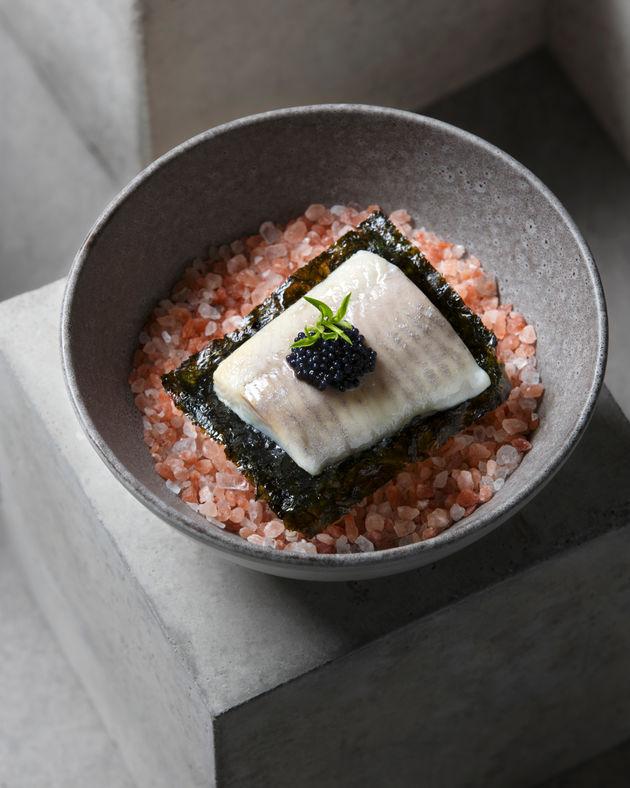 Food photography of Fish served on pink salt shot on concrete block.