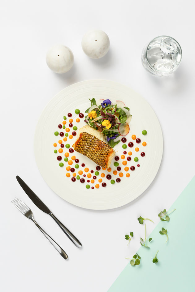 Fine dining dish with colorful sauce and amazing food styling with cutlery on white background