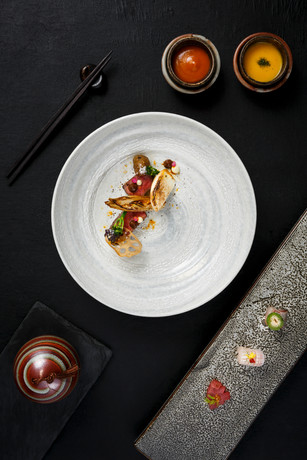 Fine dining plate with different props on black background photographed for Asia Asia restaurant