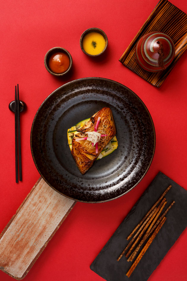 Fine dining dish with different props on red background photographed for Asia Asia restaurant