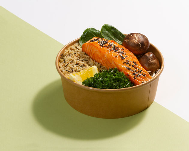 Salmon lemon kale mushroom and rice in a recyclable bowl photographed on dual color background - Bowlful Dubai