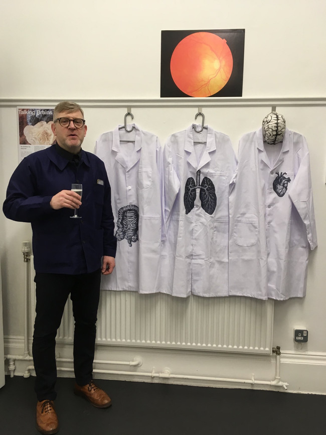 Artist next to lab coats (2018)