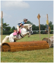 Young rider and pony clearing a jump