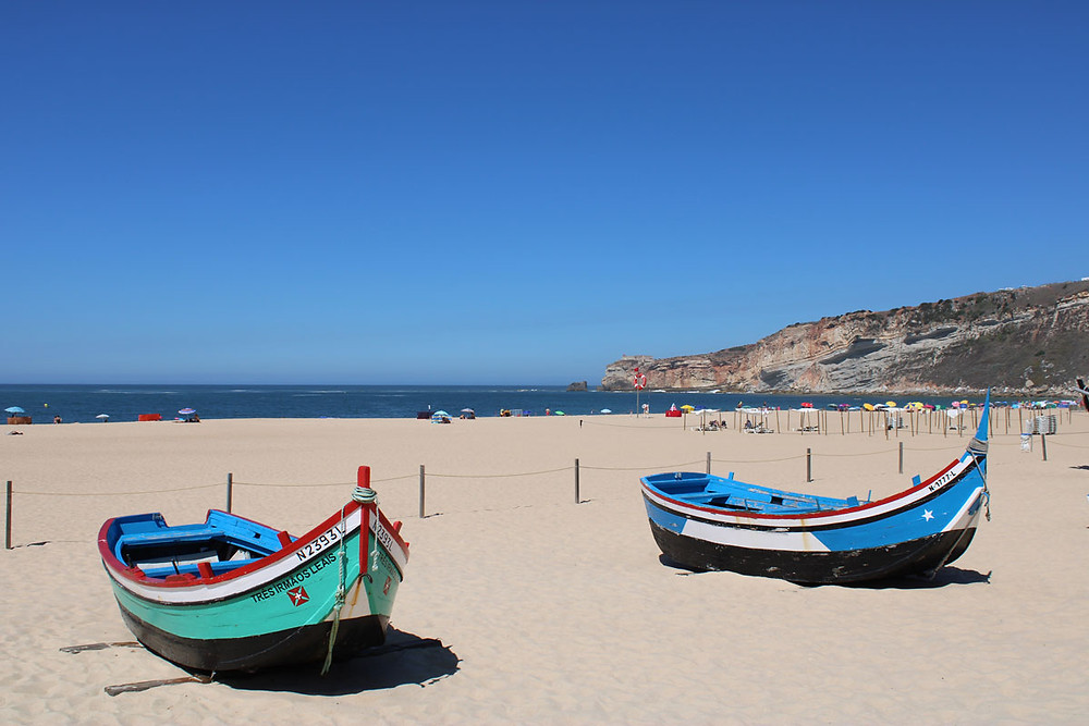 Traditional fishing boats on Nazaré beach in Silver Coast Portugal