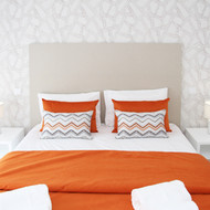 Wall paper and burnt orange colors in the bedroom