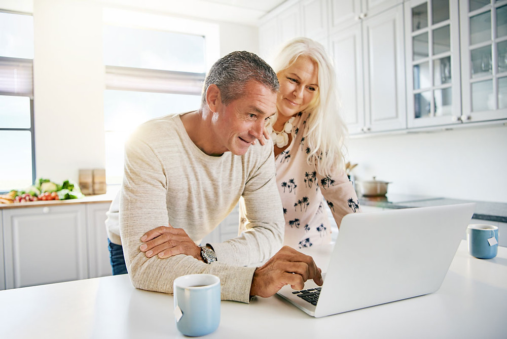 NHR Tax Regime senior couple in kitchen looking at laptop smiling