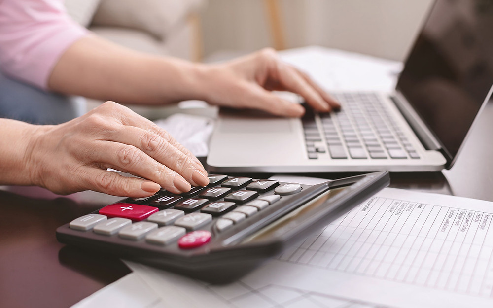 NHR Tax Regime Portugal woman's hand on calculator and laptop