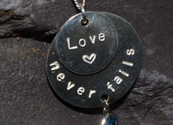 'Love never fails' stamped silver pendant with CZ