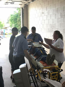 "Steve Stuart, Jake Mann, and Tyler Wise assisting a ""patient"" at a BMH training"