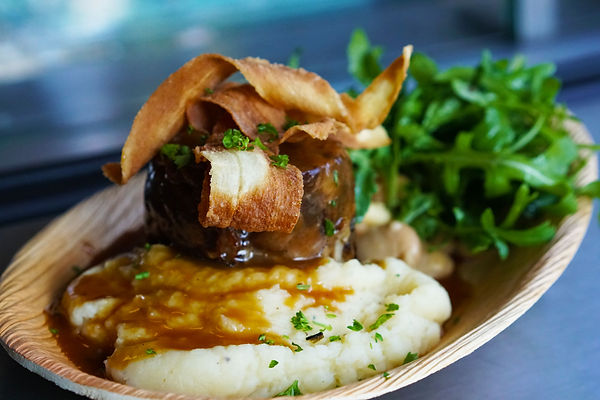 Mashed potato, Yorkshire pudding, gravy served on a wooden plate