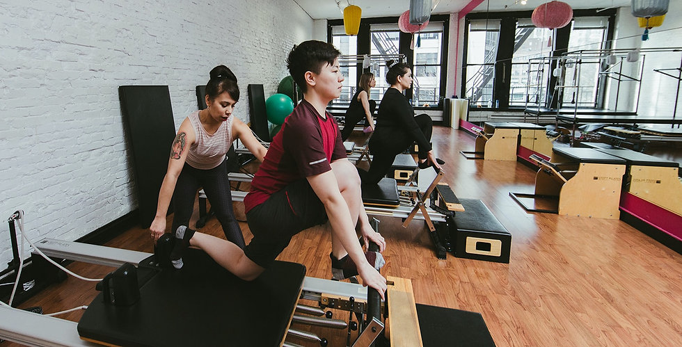 BIPOC Pilates Instructor in Seattle, WA assiting client on Pilates reformer equipment.