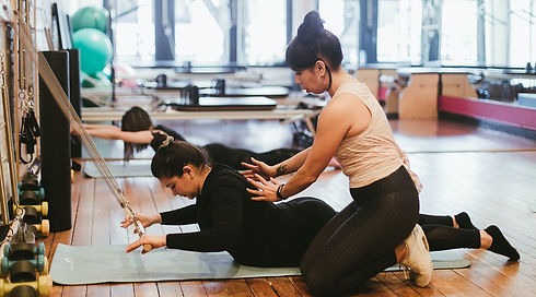 BIPOC Seattle Pilates instructor assisting client in the practice of swan exercise on the Pilates Springboard.