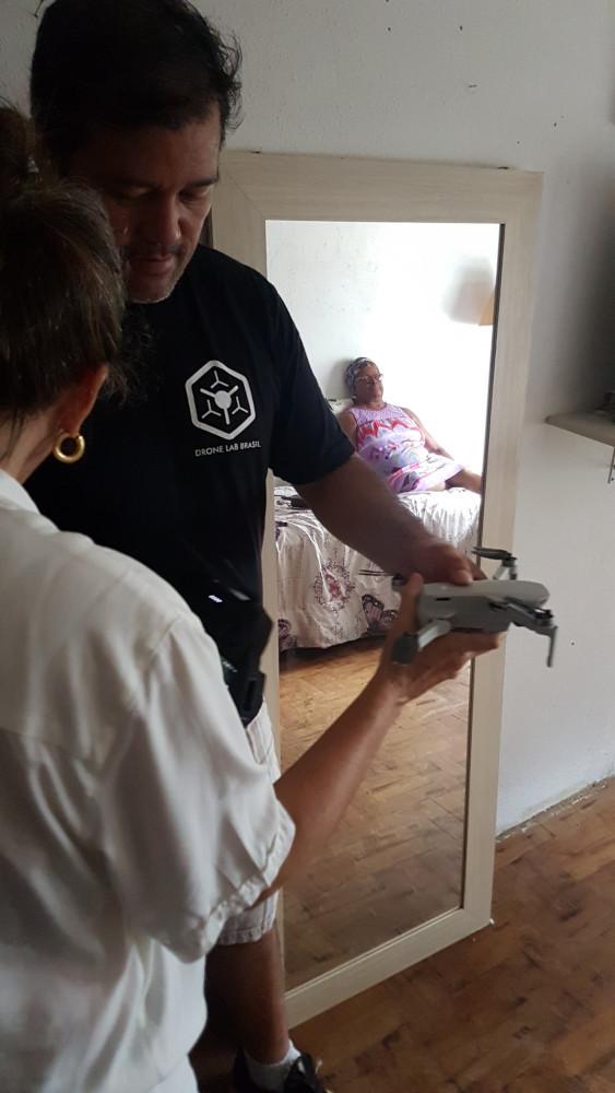 No quarto da ocupação de 2,5 por 3 metros, mais ou menos, Yamas mostra o tamanho do drone Mavic Mini para a diretora Luciana Sérvulo, mostrando que é um ótimo tamanho para fazer a gravação desejada. Detalhe do reflexo da atriz sentada na cama ao fundo aguardando a gravação.