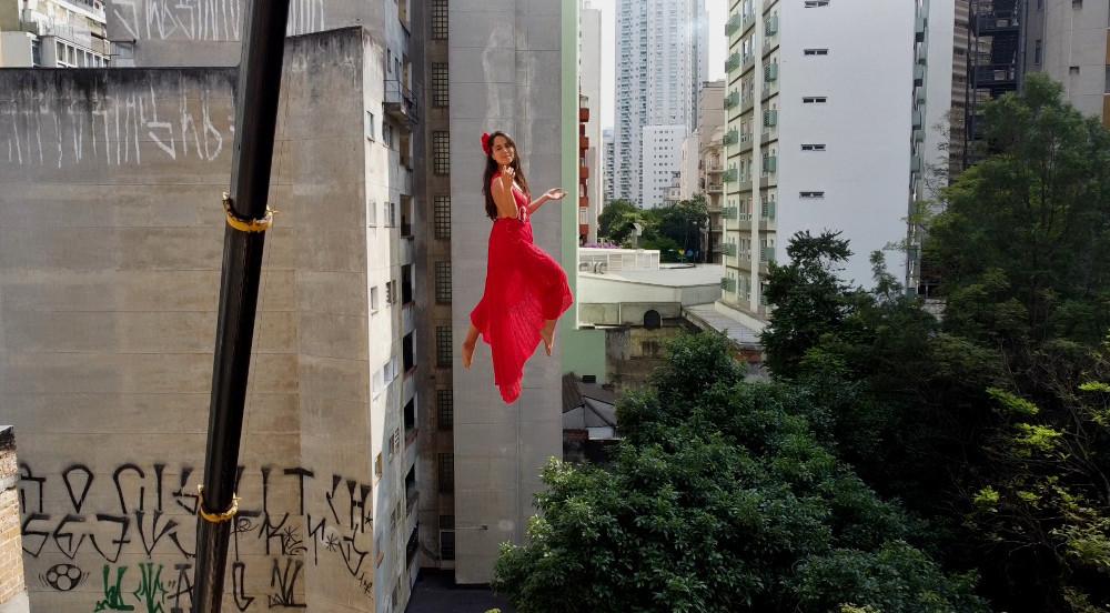 Bailarina Sandra Miyazawa fazendo uma performance a 30 metros de altura com um vestido vermelho. Ao fundo abaixo copas de árvores e prédios como pano de fundo