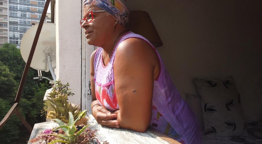 Atriz debruçada na janela é captada por Screenshot da cena em que Mavic Mini entra pela janela. No parapeito algumas plantas suculentas. A atriz é uma senhora negra e tem um lenço roxo estampado na cabeça, está com um óculos vermelho e está com um sorriso discreto na boca.