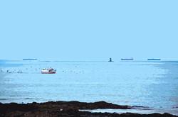 Bateau de pêche et cargos