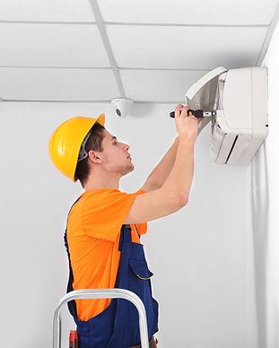 Technician repairing air conditioner on