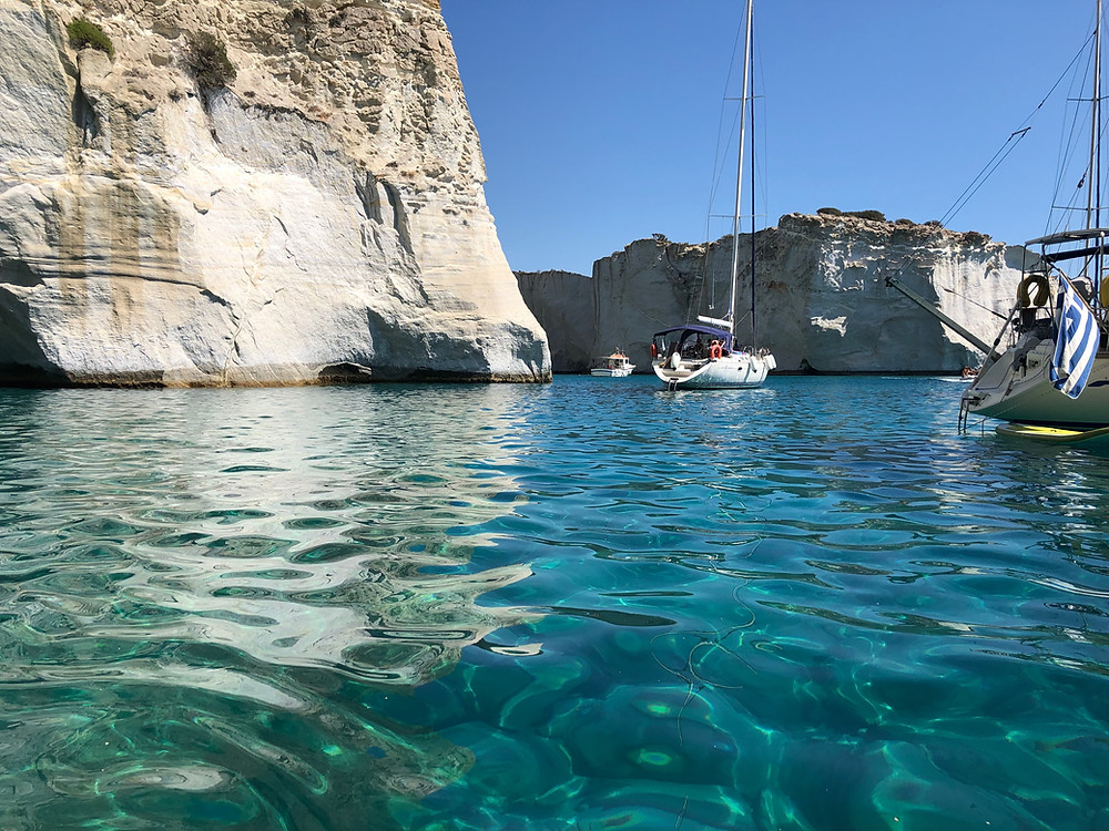 Sailing charter monohulls anchored in turquoise waters at Kleftiko, Milos island
