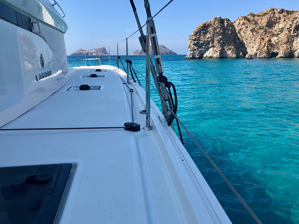Lagoon 50 charter sailing catamaran anchored at stunning Milos island cove in turquoise waters