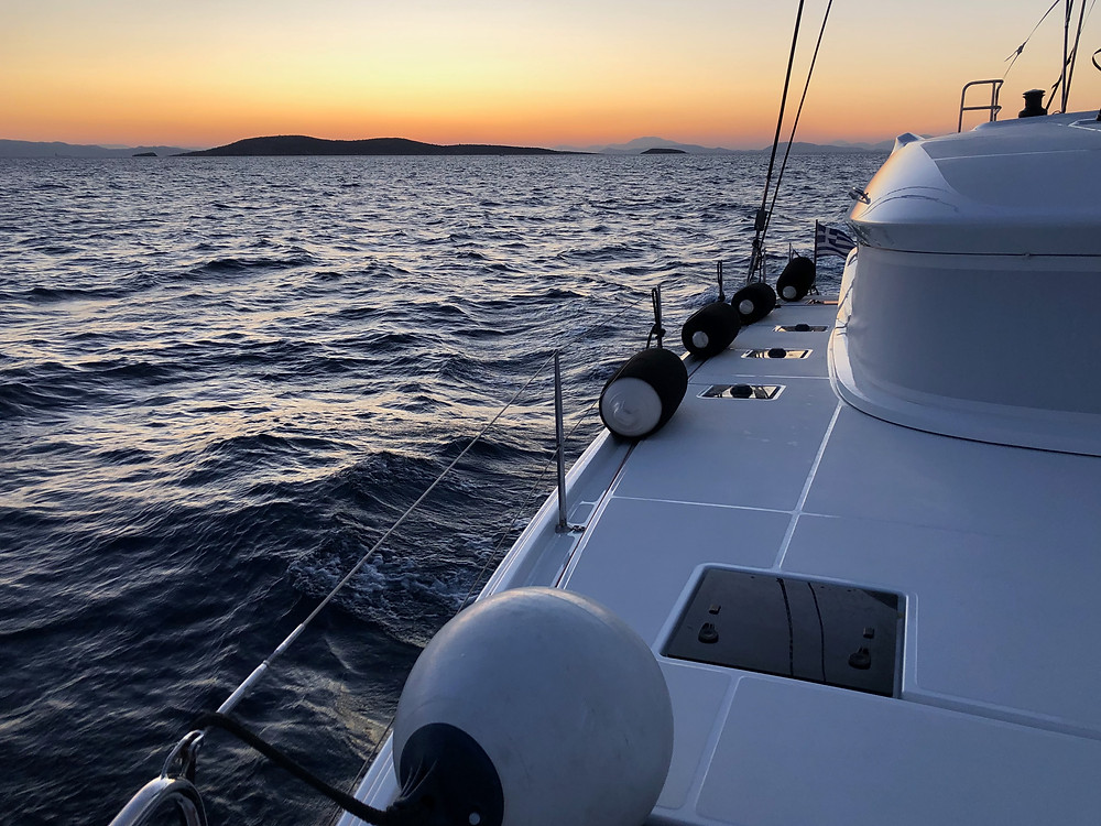 Sailing catamaran skippered charter navigating away from Athens towards Cyclades in the sunset
