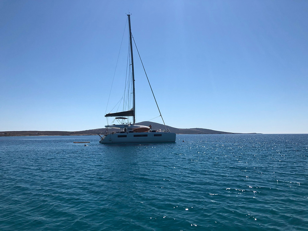 Anchored sailing catamaran chartered in the Cyclades inside a tranquil bay