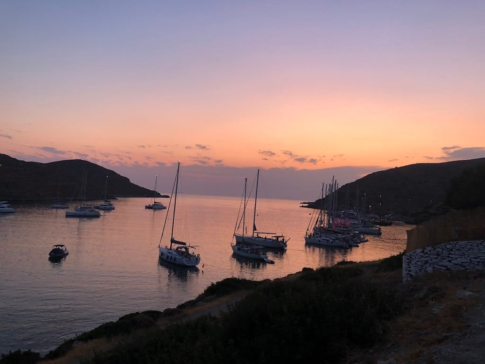 Sailing in Greece with yacht charter sailboats, anchored at a glorious bay in the Cyclades at sunset