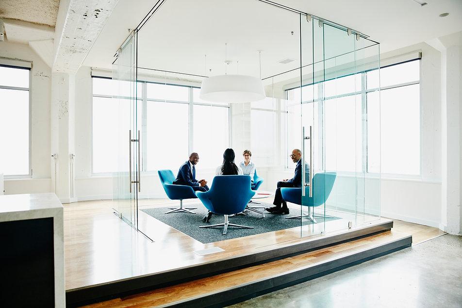 4 Menschen sitzen in einem Glasbüro
