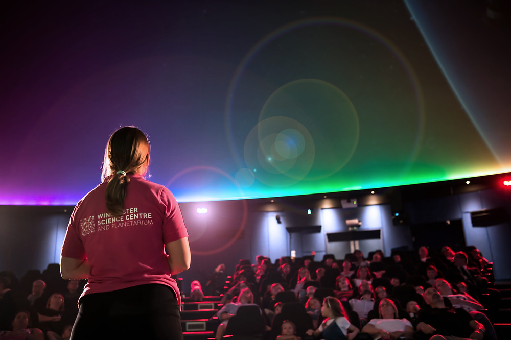 A presenter getting ready to start a planetarium show to an excited audience of families.
