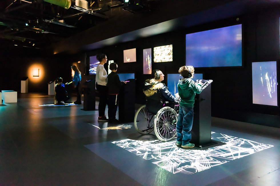 Children and adults exploring a digital science exhibit.