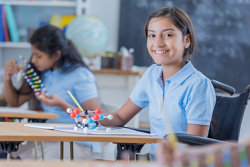 Smiling girl in a wheelchair with a chemical model