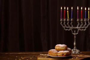 Donuts on a plate with chocolate coins and menorah