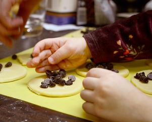 Child placing chocolate chips into Purim hamantaschen dough circles