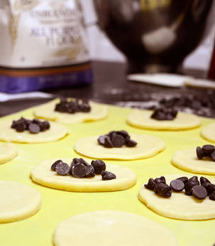 Rows of circles of dough with chocolate chips for Purim hamantaschen