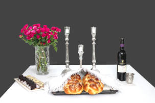 Shabbos table with pink flowers, challah, candlesticks and kiddush