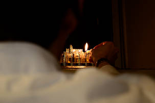 Hand lighting the menorah, view from behind