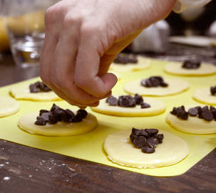 Male hand placing chocolate chips into Purim hamantaschen dough circles