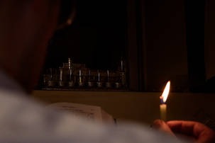 Hand holding a candle to light the menorah