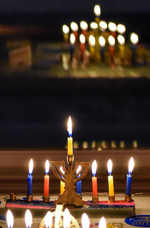 Colorful candles lit in a menorah