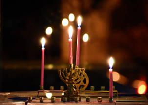 Lit menorahs with pink candles