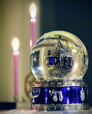 Chanukah dreidel snow globe with candles in the background