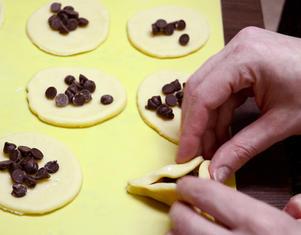 Hands forming Purim hamantaschen out of dough