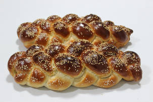 Freshly baked challah on a white background