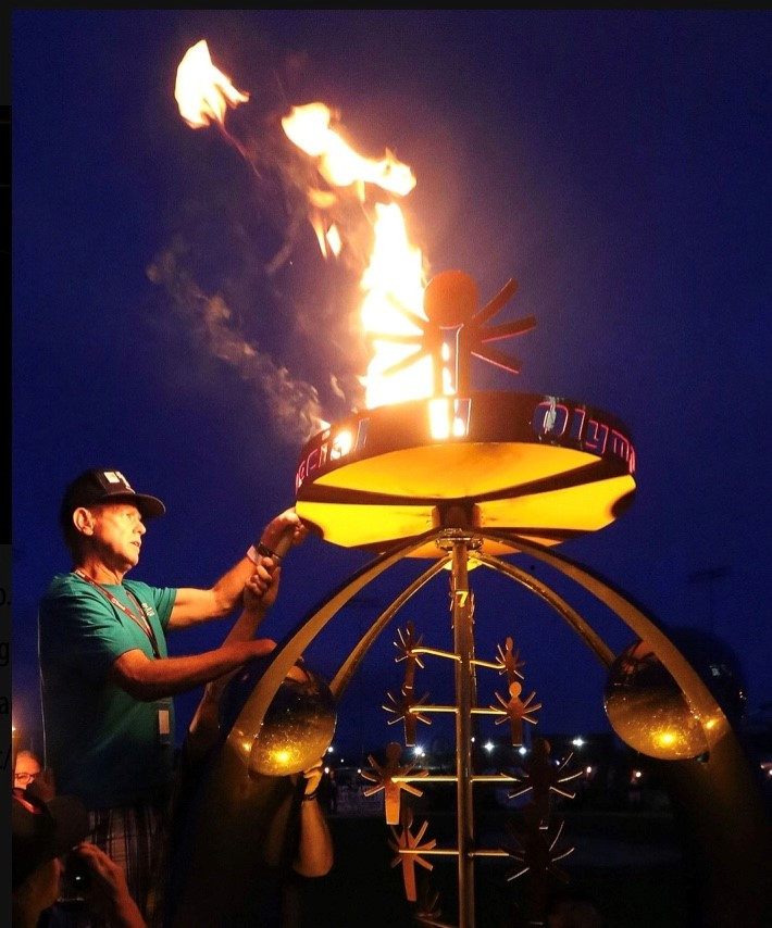 Hombre delante de una escultura en llamas