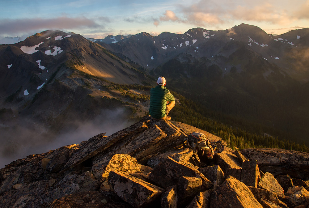 Backpacker on mountain top in wilderness of Olympic National Park in Washington.