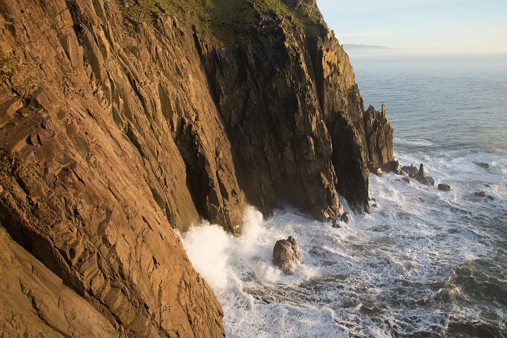 Waves crash on dramatic cliffs in Oswald West State Park in Oregon.