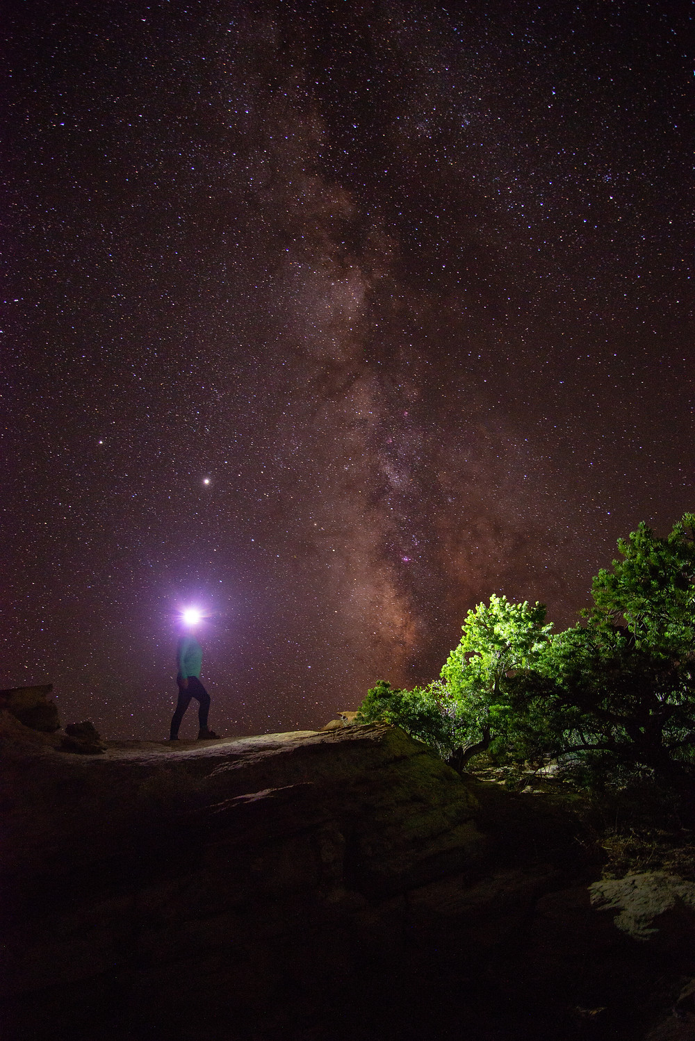 A hiker stands under the Milky Way in Capitol Reef National Park in Utah.